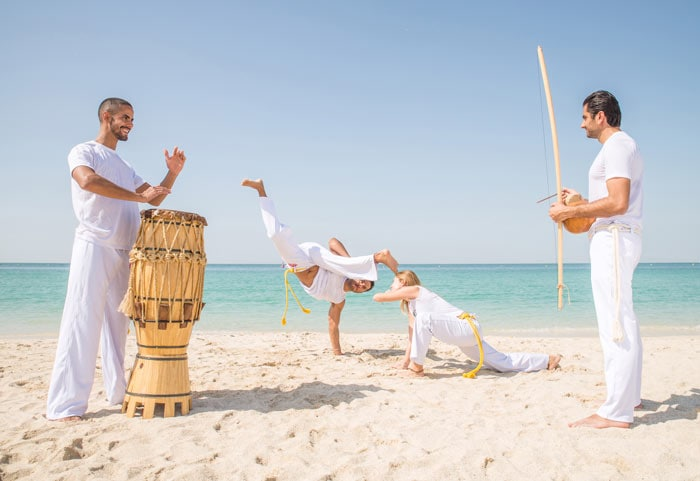 Friends training capoeira on the beach, fun activities to do in Brazil