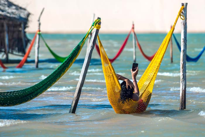 Woman chilling on hammock in Jericoacoara lagoon