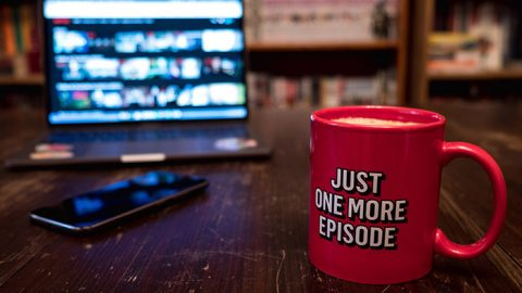 Red mug in front of television playing Brazilian shows on Netflix