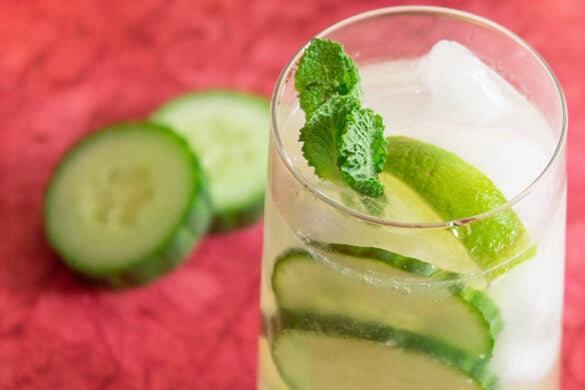 Cucumber caipiroska drink surrounded by cucumber slices