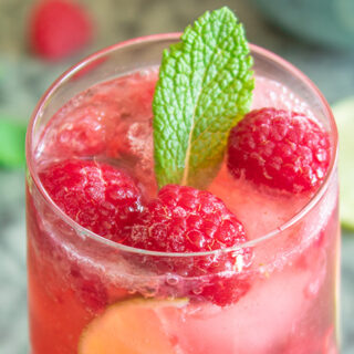 Raspberry caipiroska surrounded by raspberries and lime