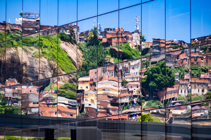 Reflection of a favela on the windows of a fancy building