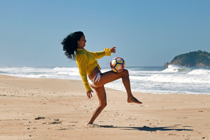 Brazilian woman playing soccer at the beach